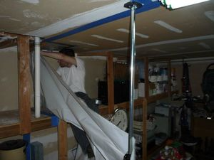 Water Damage Restoration Technician Removing Vapor Barrier
