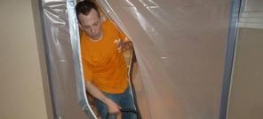 Water and Mold Damage Restoration Technician Using Air Mover Near Vapor Barrier